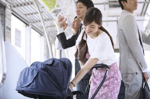 電車の中で赤ちゃんをあやす母親の写真素材 [FYI02970557]