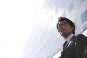 ビルの前で遠くを見るビジネス男性の写真素材 [FYI02970569]