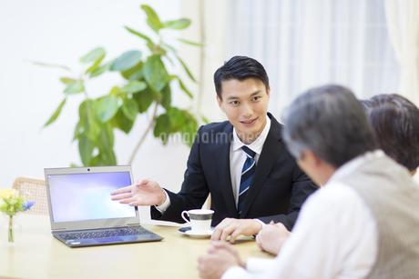 シニア夫婦に説明する訪問営業の男性の写真素材 [FYI02970613]