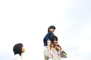 草原で娘を肩車する父と付き添う母の写真素材 [FYI02970632]