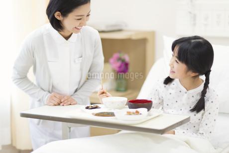病室で話をする女の子と女性看護師の写真素材 [FYI02970666]