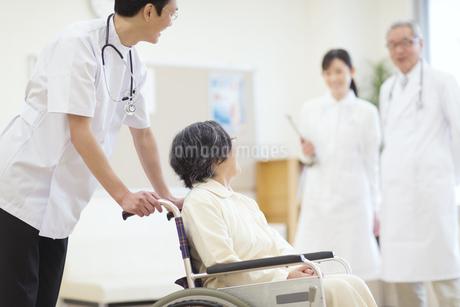 車椅子の患者に添う男性医師の写真素材 [FYI02970700]