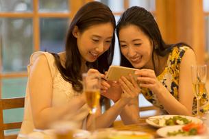 スマートフォンで楽しむ2人の女性の写真素材 [FYI02970717]