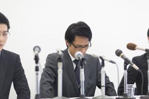 会見で頭を下げるビジネス男性の写真素材 [FYI02970744]