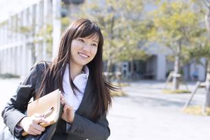 手帳を手に微笑むビジネス女性の写真素材 [FYI02970753]