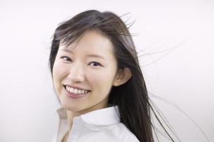 風を受けながら微笑む女性のアップの写真素材 [FYI02970756]