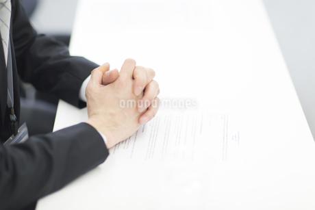 書類の上で組まれたビジネス男性の手の写真素材 [FYI02970761]