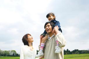 草原で娘を肩車する父と付き添う母の写真素材 [FYI02970801]
