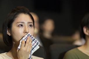 映画館で涙をこぼす女性の写真素材 [FYI02970823]