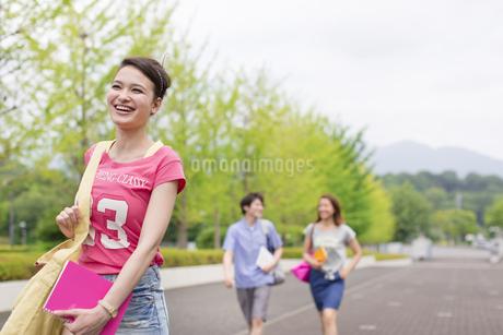 微笑みながらキャンパスを歩く女子学生の写真素材 [FYI02970831]