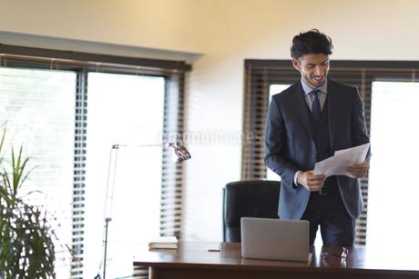 オフィスで資料を持ち微笑むビジネス男性の写真素材 [FYI02970834]