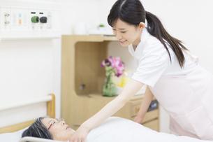患者に布団をかける女性看護師の写真素材 [FYI02970837]