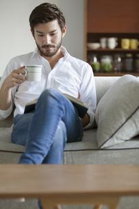 ソファーに座りカップを手に持って本を読む男性の写真素材 [FYI02970838]