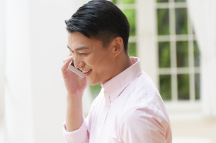 スマートフォンで会話をする男性の写真素材 [FYI02970840]