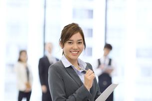 オフィスビルのロビーで資料を持って微笑むビジネス女性の写真素材 [FYI02970851]