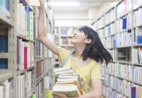 図書室で棚から本を引き出す女子学生の写真素材 [FYI02970860]
