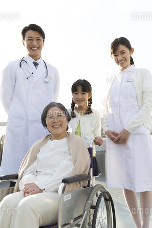 屋上で車椅子の患者に添う医師と看護師と女の子の写真素材 [FYI02970861]
