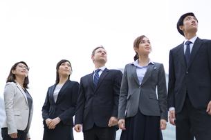 オフィスビルを背景に上を見上げて立つビジネス男女の写真素材 [FYI02970862]