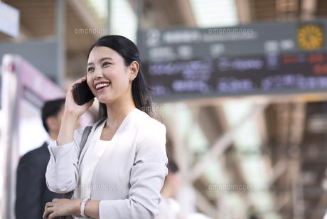 駅のホームで電話をするビジネス女性の写真素材 [FYI02970863]
