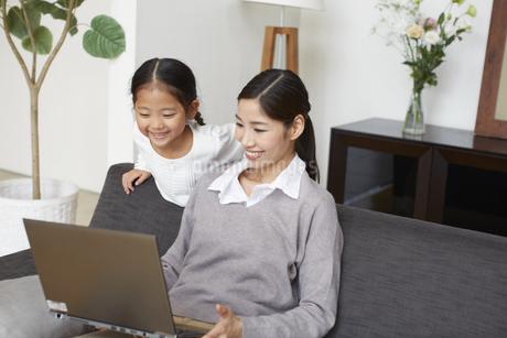 ソファーでノートパソコンを見る母と子の写真素材 [FYI02970864]