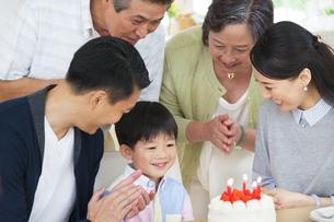 ケーキを前に誕生日のお祝いをする家族の写真素材 [FYI02970869]