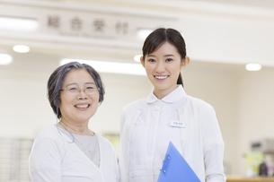 受付前で微笑む患者と女性看護師の写真素材 [FYI02970872]