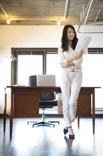 オフィスで資料を手に持ち微笑むビジネス女性の写真素材 [FYI02970873]