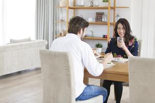 ダイニングテーブルで食事を楽しむ男性と女性の写真素材 [FYI02970875]