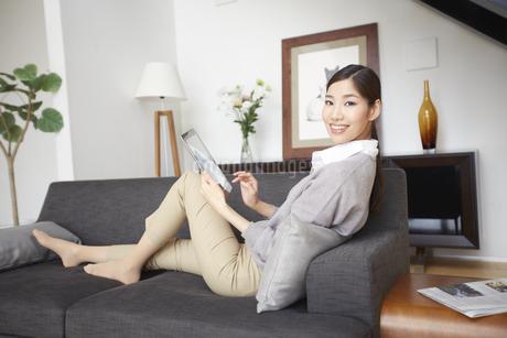 ソファーでスマートデバイスを持つ女性のスナップの写真素材 [FYI02970876]