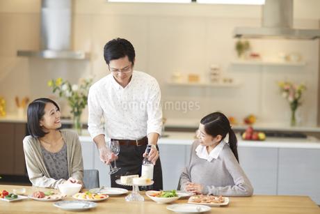 女性二人の間にワインを置く男性の写真素材 [FYI02970877]