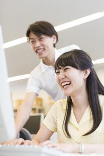 パソコンに向いて笑う2人の学生の写真素材 [FYI02970878]