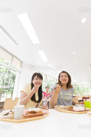 学食で食べながら笑う学生たちの写真素材 [FYI02970879]