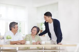 ダイニングテーブルで談笑するシニア夫婦と息子の写真素材 [FYI02970883]