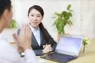 説明する訪問営業の女性と話を聞く男性の写真素材 [FYI02970884]