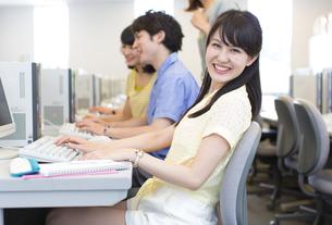 パソコンを前に微笑む女子学生のポートレートの写真素材 [FYI02970885]