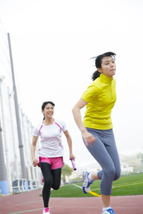 陸上競技場でバトンの手渡しをする女子学生たちの写真素材 [FYI02970887]