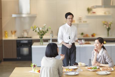 料理の前で会話する女性とワインを運ぶ男性の写真素材 [FYI02970888]