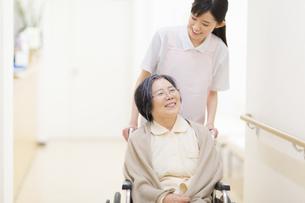 車椅子の患者を押す女性看護師の写真素材 [FYI02970894]