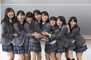 黒板の前に笑顔で並ぶ女子高校生たちのポートレートの写真素材 [FYI02970895]