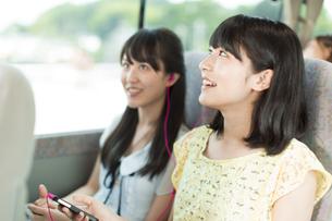 バスの車中でイヤホンをする2人の女性の写真素材 [FYI02970897]