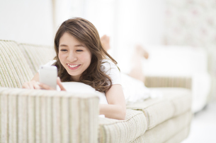 ソファの上でスマートフォンを見る女性の写真素材 [FYI02970901]