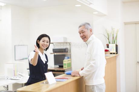 笑顔でシニア男性を案内をする女性の写真素材 [FYI02970904]
