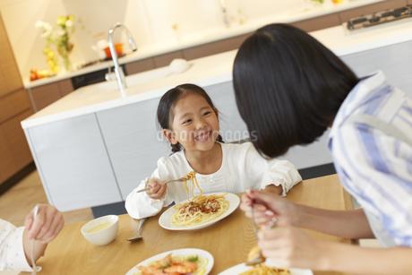 食事をしながら母に向いて笑う女の子の写真素材 [FYI02970906]