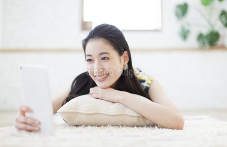 クッションの上でタブレットPCを見る女性の写真素材 [FYI02970907]