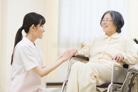 車椅子の患者の手に手を添える女性看護師の写真素材 [FYI02970909]