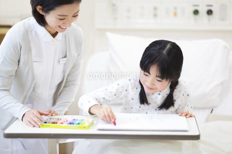 病室でお絵かきを楽しむ女の子と女性看護師の写真素材 [FYI02970920]