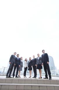 オフィスビルを背景に上を見上げて立つビジネス男女の写真素材 [FYI02970924]