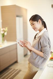 キッチンでスマートフォンを操作する女性の写真素材 [FYI02970936]