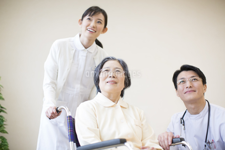 車椅子の患者に添う男性医師と女性看護師の写真素材 [FYI02970943]