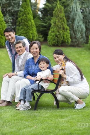 ベンチに揃って笑顔の三世代家族の写真素材 [FYI02970947]